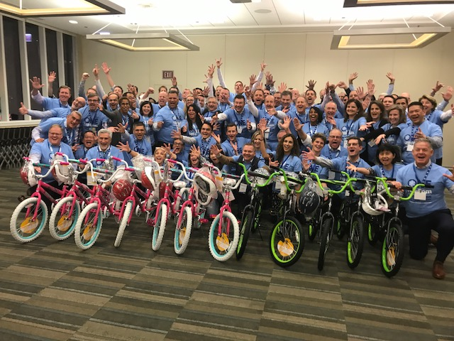 A group of team members pose for a Build-A-Bike charity activity