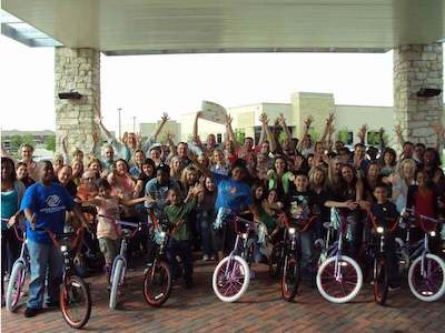 Children and team pose for a photo after a Charity Build-A-Bike event.