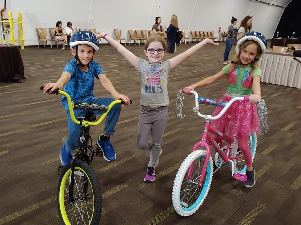 Children receiving bikes from a charity team building event.
